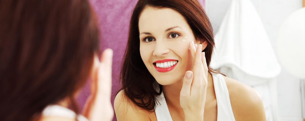 Woman smiling in mirror while putting on cream