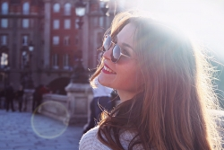 brunette woman wearing sunglasses stood in the sun